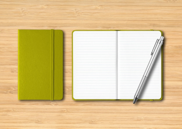 Olive green closed and open lined notebooks with a pen. mockup isolated on wooden background