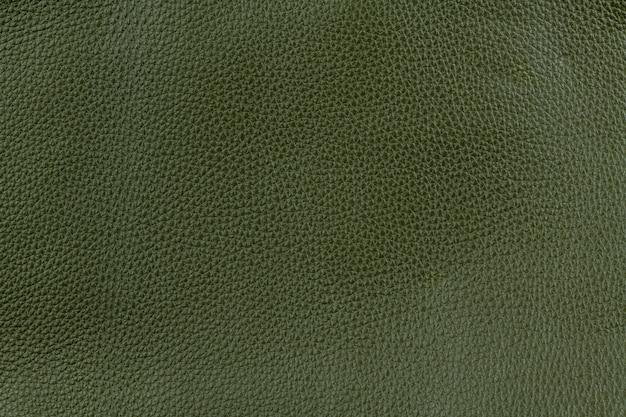 ミディアムグレインテクスチャバックグラウンドでオリーブグリーンの滑らかな天然皮革