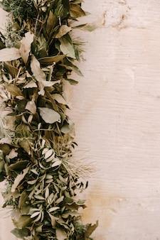 올리브 뉴스 종려 나무 침엽수 월계수 잎과 thuja 가지가 하나의 번들 크리스마스로 짜여져 있습니다.