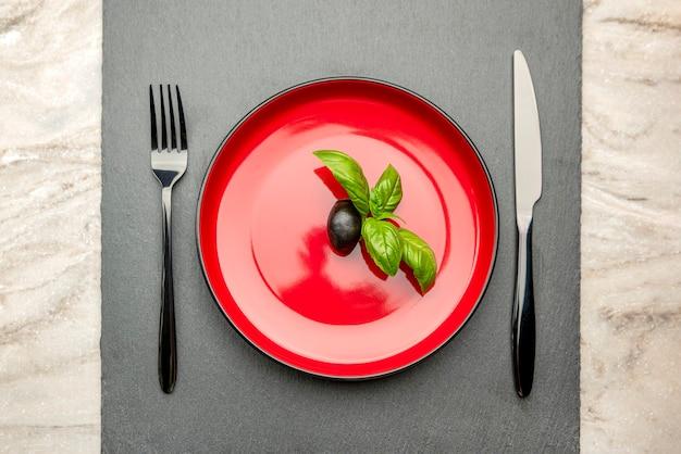 オリーブオイル。女性が受け皿にオリーブオイルを注ぎます。
