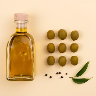 Оливковое масло и зеленые оливки вид сверху