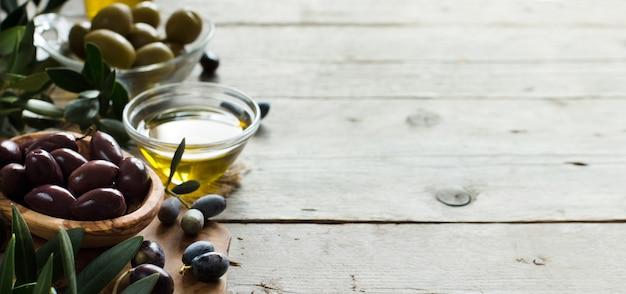 Оливковое масло и оливки на деревенском деревянном фоне