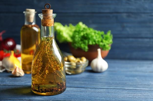 Оливковое масло и некоторые специи на деревянных