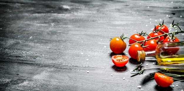 枝にオリーブオイルとトマト。黒の素朴な背景に。