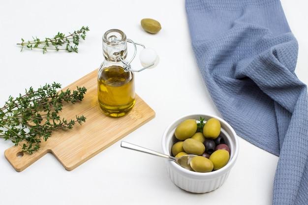 Бутылка оливкового масла и веточки тимьяна на борту. оливки в керамической миске. серая салфетка на столе. вид сверху.