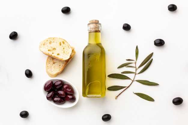 Olive oil bottle bread slices and purple olives