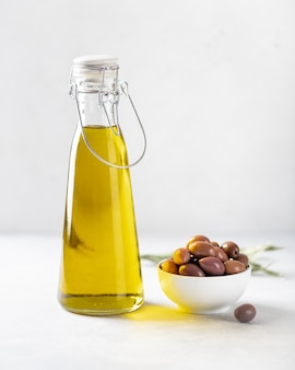 Olive oil in a bottle and kalamata olives on white background, selective focus