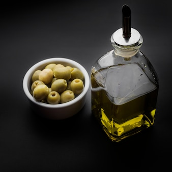 Olive oil bottle and olives on kitchen counter
