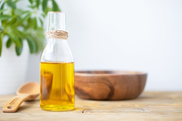 Olive oil in a bottle, a spoon, a plate and a flower in a pot on a wooden table on a white background. copy space.