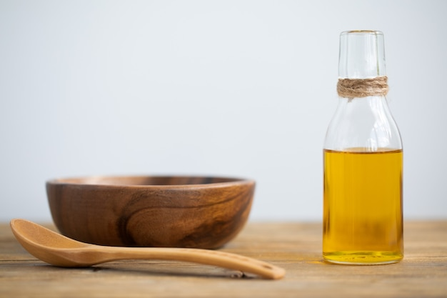 Olive oil in a bottle, a spoon, a plate on a wooden table on a white background. copy space.