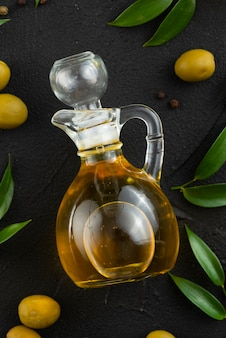 Olive oil bottle on table with leaves and olives