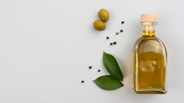 Бутылка оливкового масла с листьями и оливками на столе