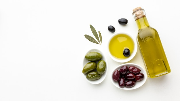 Olive oil bottle with leaves and green purple olives with copy space