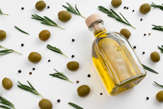 Olive oil bottle with olives and leaves around