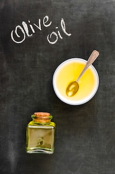 Olive oil in bowl and bottle closed with cork on blackboard
