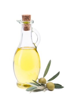 Olive oil in a glass bottle, fresh olives and olive branch.