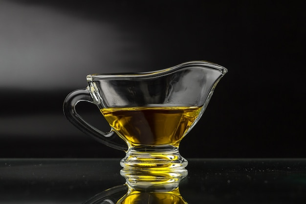 Olive oil in a glass gravy boat on a black surface