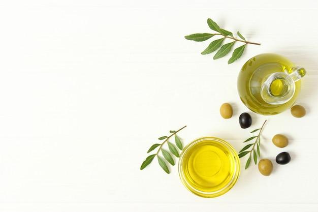 Зеленые листья оливкового масла и оливки на столе