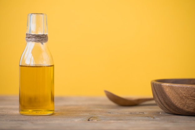 병에 든 올리브 오일, 숟가락, 노란색 배경에 있는 나무 테이블에 있는 접시. 공간을 복사합니다.