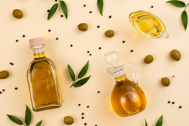 Оливковое масло в бутылках и чашка на столе