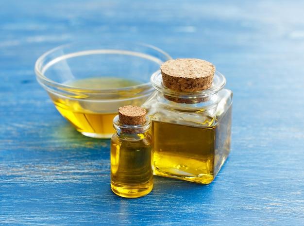 Оливковое масло в бутылках на синем фоне крупным планом