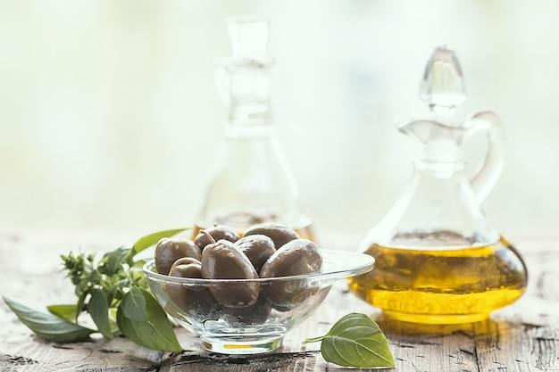 ガラス瓶のオリーブオイルと古い木製のテーブルの上のオリーブ