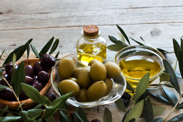 Olive oil and olives on rustic wooden table