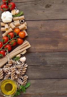 オリーブオイル、パスタ、ニンニク、トマト、茶色の木製のテーブル