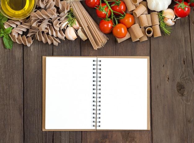 オリーブオイル、パスタ、ニンニク、トマトの木製テーブルの上のblocknoteのトップビュー