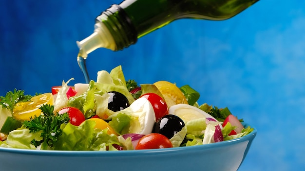 Olive oil pouring from bottle onto vegetable salad, healthy and dietary food from fresh ingredients in bowl on blue background