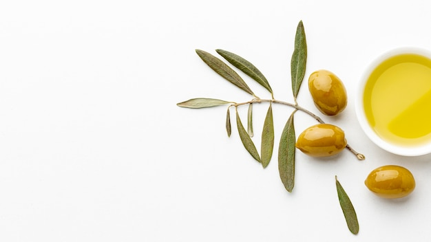 Olive oil saucer with leaves and yellow olives with copy space