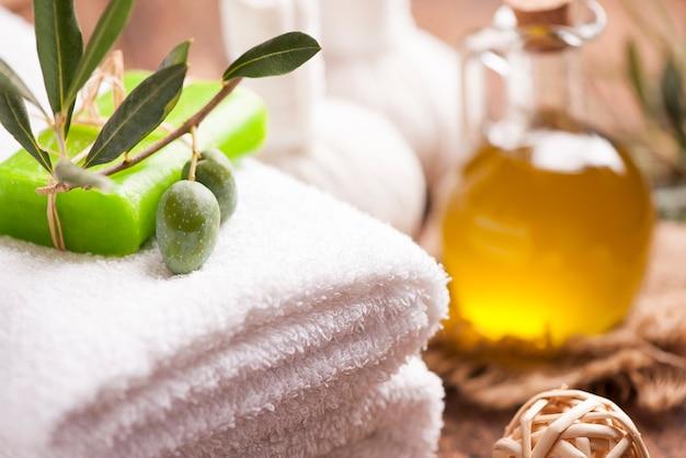 나무 테이블에 올리브 오일 비누와 목욕 수건