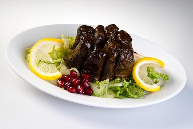 Фаршированные оливковым маслом листья на тарелке с овощами для обслуживания для концепции ресторана из турции