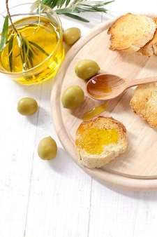 Olive oil with bread and wooden spoon