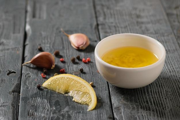 Оливковое масло с чесноком и лимоном в белой миске на деревенском столе. заправка для диетического салата.