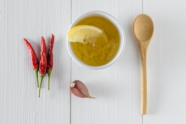 Оливковое масло с чесноком, красным перцем и лимоном и петрушкой в миску белого на белом столе. заправка для диетического салата. вид сверху.