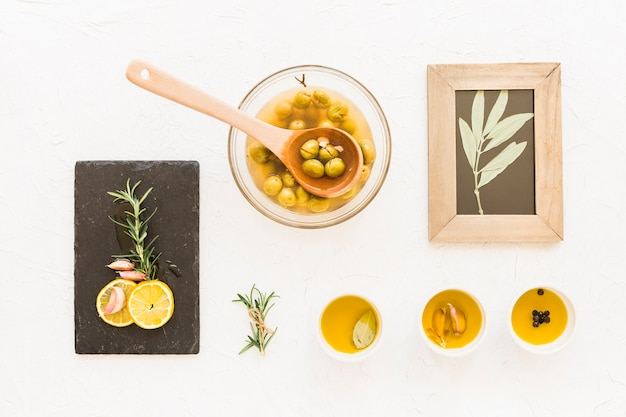Olive oils with twig wooden frame on white background