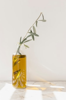 Olive twig inside the yellow oil in the glass bottle on the marble floor