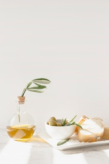 Olive with slice of bread and bottle of oil against white wall