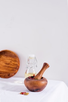 Olive wooden mortar and pestle with chili peppers and cardamom isolated on textile table, copy space