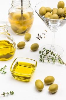 Оливки и оливковое масло на белом столе. закройте вверх. вид сверху