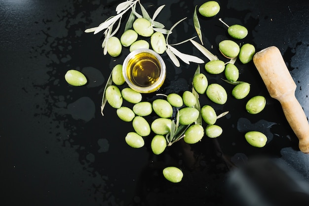 Olives around glass with olive oil