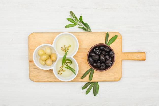 Ассортимент оливок и оливковое масло с оливковыми листьями в миску и разделочную доску на белой древесине, вид сверху.