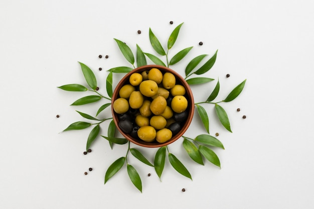 Olives in bowl with leaves next on table
