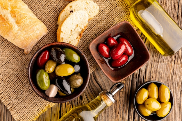 Olives in bowls bread and wooden spoon on textile material