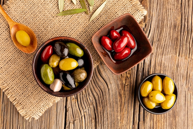 Olives in bowls and wooden spoon on textile material