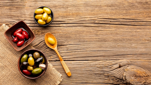 Olives in bowls and wooden spoon with copy space