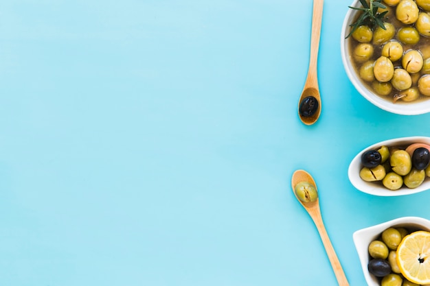 Olives in different bowls and two wooden spoon over the blue background