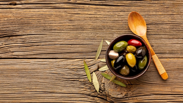Olives mix and wooden spoon with copy space