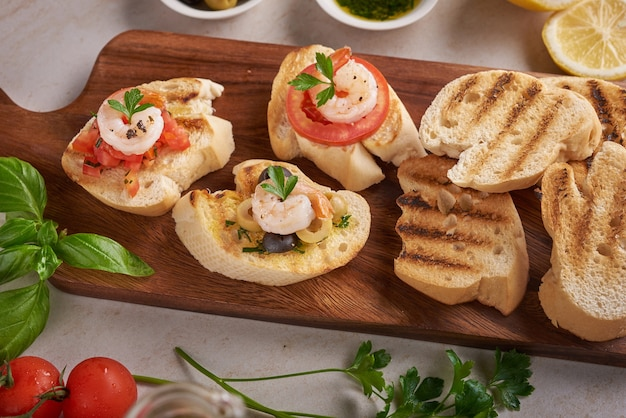 Olives, oil, grilled shrimps and fresh vegetable salad on a wooden board on black slate stone board over dark surface, juicy tomatoes on fresh bread, pesto as topping. top view. flat lay